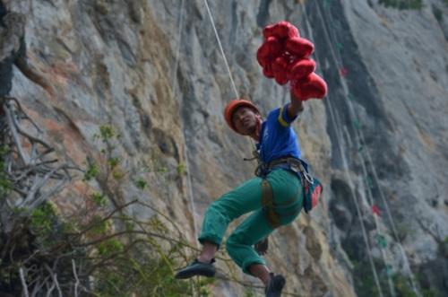 2 主定线员摘下岩壁爱心,象征着公益金(物)的捐献。陆丽红 摄 中国登山协会供图