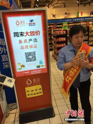 超市工作人员在给顾客讲解如何使用自助结账服务。<a target='_blank' href='http://www.chinanews.com/' >中新网</a> 吴涛 摄