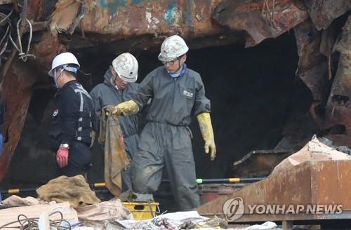 """5月12日,""""世越""""号现场处理本部工作人员在船尾发现疑似失踪者遗骨。(图片来源:韩联社)"""