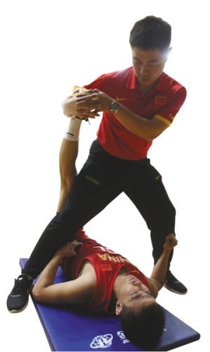 红队训练结束后,赵继伟在队医的帮助下拉伸大腿。 新京报记者 王飞 摄