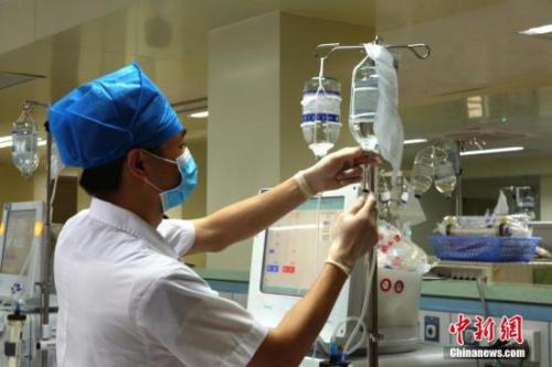 资料图:医护人员在用针管抽取药剂。朱柳融 摄