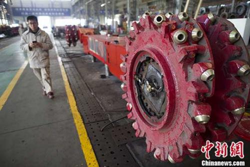 图为山西太重工人从采煤机前颠末。(资料图片) /p中新社记者 张云 摄