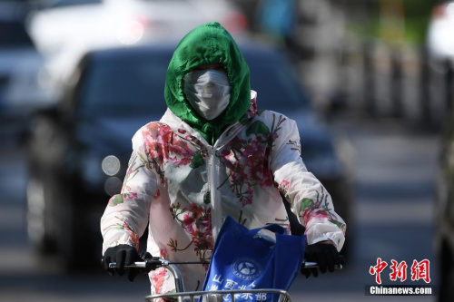 """5月17日,山西太原,民众在烈日下""""全副武装""""出行。武俊杰 摄"""