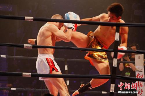 """图为绰号""""幽灵刺客""""的中国拳手刘奇良(右)向加拿大拳手发起攻势。 中新社记者 余瑞冬 摄"""