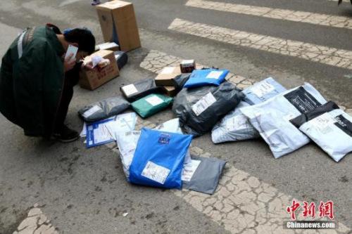 资料图:快递员在打电话联系买家。<a target='_blank' href='http://www.chinanews.com/'>中新社</a>记者 张远 摄