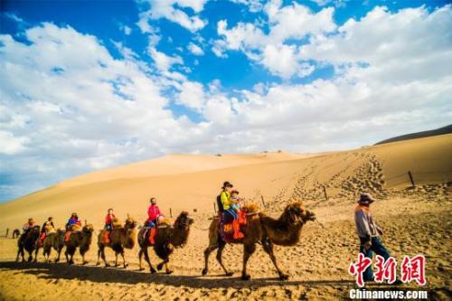 资料图:游客骑骆驼在鸣沙山景区观光游览。 王斌银 摄