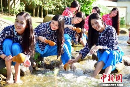 资料图:姑娘在湖边洗发。 曾令华 摄