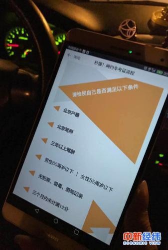 小李拿手机展示滴滴平台的网约车司机标准 中新经纬 吴一尘 摄