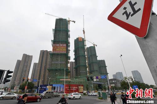 资料图:商品房在建中。 中新社记者 吕明 摄