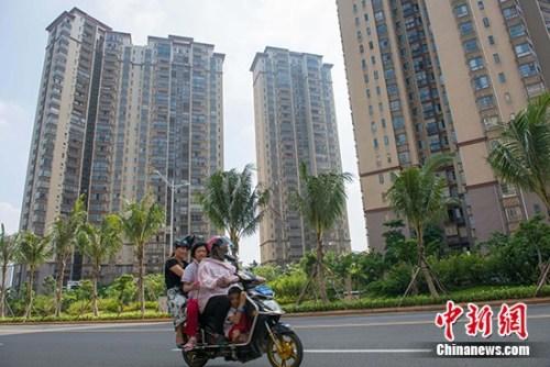 资料图:市民在某地产项目前路过。 中新社记者 骆云飞 摄