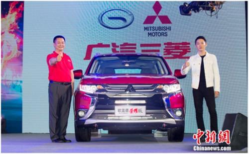 广汽三菱汽车有限公司副总经理、三菱汽车销售(中国)有限公司董事长杜志坚 (左)歌手梁博(右)与欧蓝德荣耀版合影