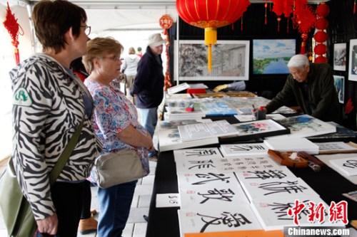 当地时间5月21日,在郁金香节中国文化综合展台,98岁华人国画家李公扬(右)现场挥毫作画,吸引宾客驻足。中新社记者 余瑞冬 摄