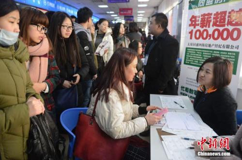 资料图:2月15日,山西太原,春节后首场高校毕业生招聘会开场,图为众多求职者被一家公司的高薪待遇吸引。韦亮 摄