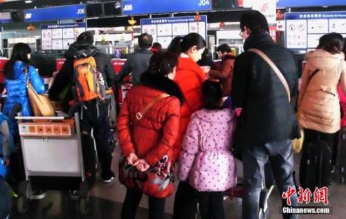 北京首都机场国际机场的乘客在排队办理登机手续。(资料图)中新社发 钱兴强 摄