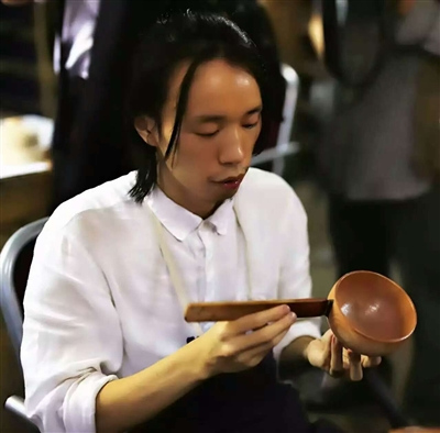 留长发的吴劲松正在刷漆 受访者供图
