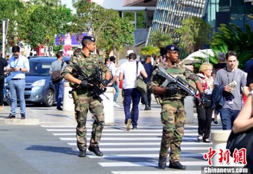 英国曼彻斯特爆炸事件发生后,法国戛纳国际电影节已经将安全戒备提升至最高状态。图为荷枪实弹的巡逻士兵在戛纳电影宫前戒备。中新社记者 龙剑武 摄