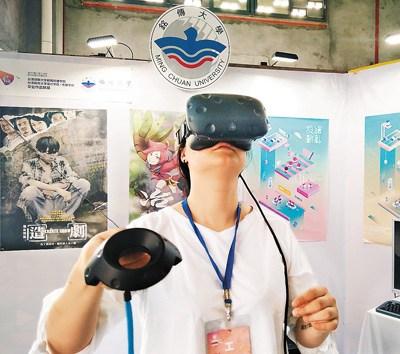 图为活动中一名女同学头戴学生自制的VR设备体验虚拟现实场景。 徐 林摄