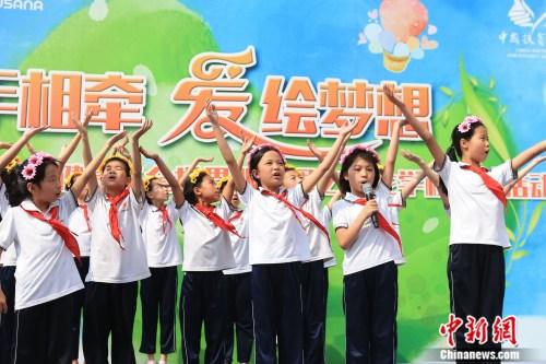 在校学生为现场志愿者演唱六一歌曲