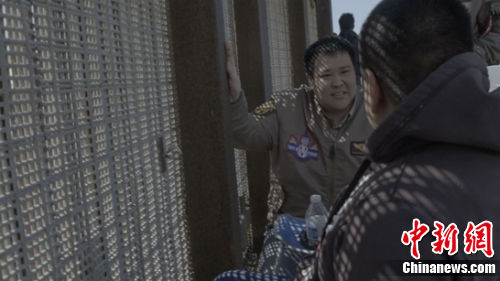张昕宇与边境墙边的一位父亲聊天