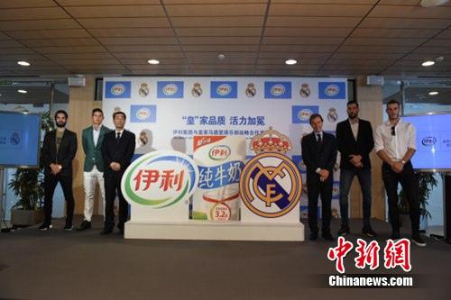 伊利集团执行总裁张剑秋(左三)与皇马相关负责人及贝尔、J罗等球员共同揭秘伊利牛奶产品