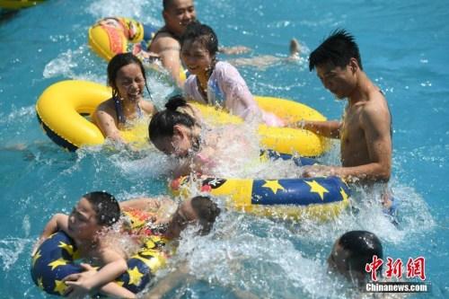 资料图:5月27日,重庆洋人街一水上乐园吸引不少市民玩水纳凉。当日,重庆主城区室外最高气温逼近35℃。 陈超 摄