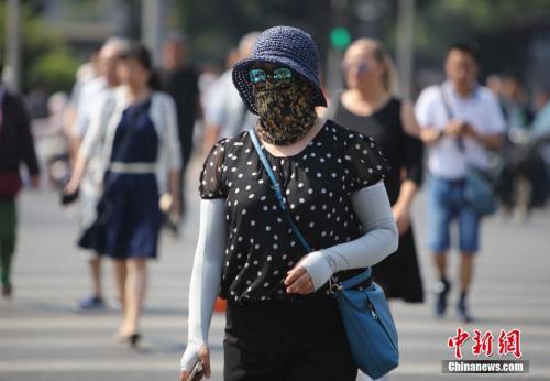 资料图:5月17日,北京街头的民众防晒出行。当日北京市气象台发布今年首个高温黄色预警。<a target='_blank' href='http://www.chinanews.com/'>中新社</a>记者 杨可佳 摄