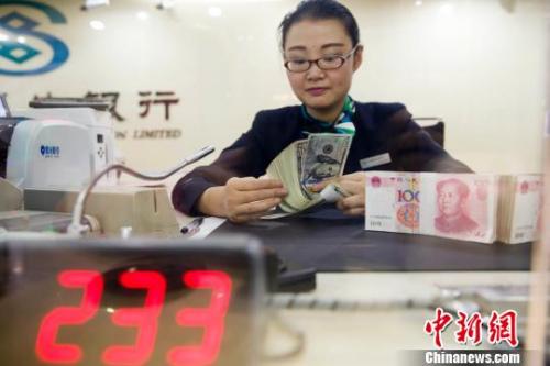 资料图:银行工作人员正在清点货币。 张云 摄