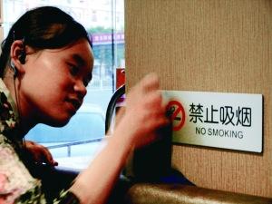 昨日,在北京西城某餐厅店员正在擦拭禁止吸烟标志。北京晨报记者 姜浩波/摄