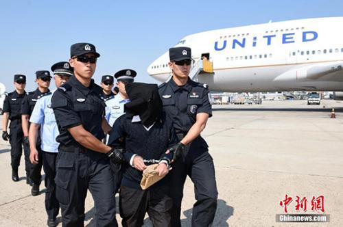 6月1日,中国籍严重刑事犯罪嫌疑人朱某在北京首都国际机场停机坪被警方验明身份后带走。 中新社记者 侯宇 摄