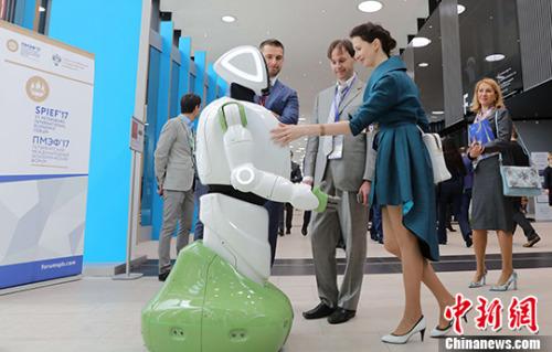 当地时间6月1日,几名与会者在与展出的人形机器人进行交流。 中新社记者 王修君 摄