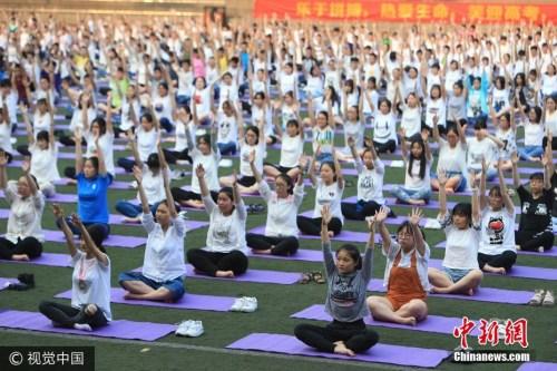 2017年5月19日,在重庆铁路中学,千余名高三学生通过在操场上练习瑜伽,来缓解高考前的焦虑和疲劳。风 摄 图片来源:视觉中国