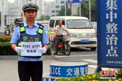 资料图:2016年6月6日,湖北省宜昌市公安局交警支队在城区7个考点安排专人指挥交通,执勤民警也在考点前拍下自拍照片,祝愿考生实现梦想。宜交宣 供图