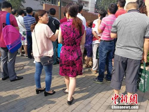 6月7日,人大附中考场外,一名家长身着旗袍送考。 中新网记者 张尼 摄