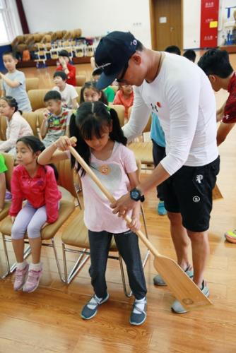 龙舟队员手把手教孩子使用龙舟桨。组委会供图