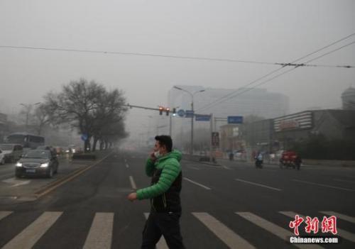 资料图:一名戴着口罩的行人走在北京街头。<a target='_blank' href='http://www.chinanews.com/'>中新社</a>记者 张浩 摄