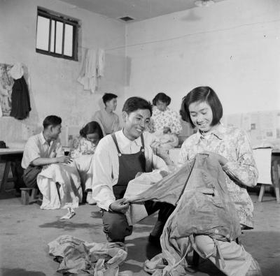 """1957年6月,为节约棉布支援工业生产,华北直属工程公司工人们提出""""一年不领工作服"""",依靠缝补克服困难。高宏/摄"""