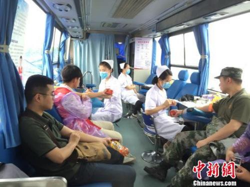 图为民众在献血车上献血。 吴鹏泉 摄