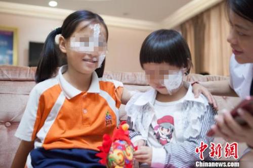 图为两名受伤女童相互鼓励。 王华 摄
