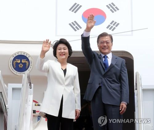 6月28日下午,在首尔机场,韩国总统文在寅(右)和第一夫人金正淑登机之前挥手致意。(韩联社)
