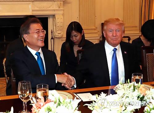 当地时间6月29日,在美国白宫,韩国总统文在寅(左)与美国总统特朗普在晚宴开始前握手合影。(韩联社)