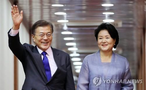 7月2日下午,在首尔机场,韩国总统文在寅(左)和第一夫人金正淑抵达首尔后挥手致意。(韩联社)