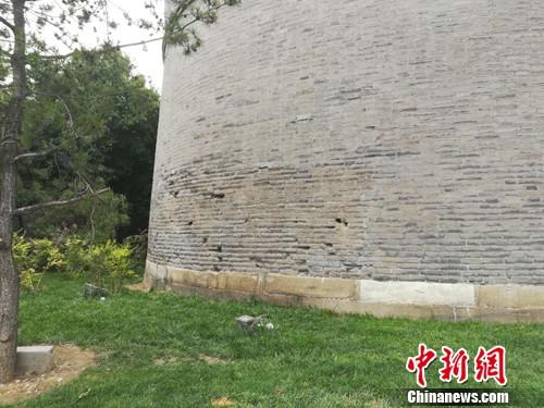 """宛平城墙上的坑孔。有一位老人说,这是当年""""七七事变"""",日军炮击宛平城留下的弹孔。上官云 摄"""