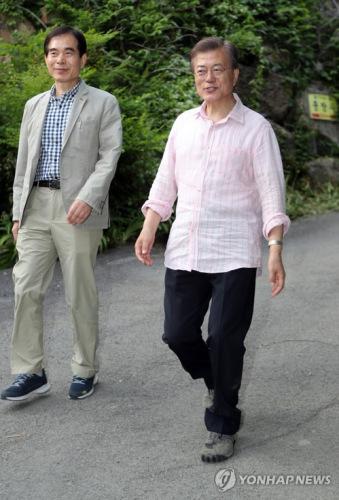 資料圖片:5月21日下午抵達位於慶尚南道梁山市的私邸準備度假的韓總統文在寅(右)與總統警衛室長朱英訓(韓聯社)