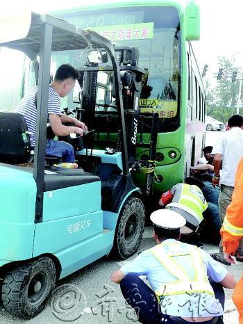 公交 女子 车底 卷入 叉车/女子被卷入公交车底,救援人员找来起重气垫和叉车救人。消防供...