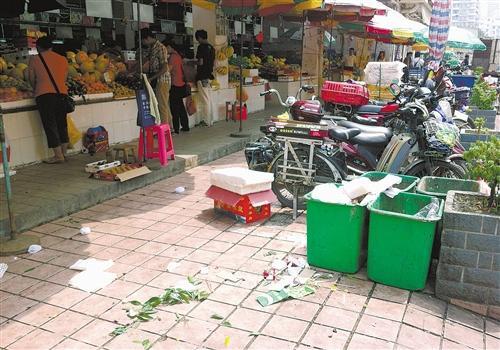 埌西农贸市场水果摊前的垃圾桶周围垃圾满地