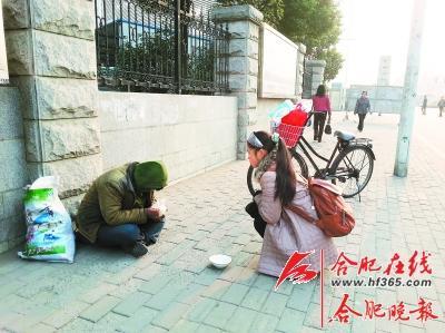 ○女孩将热气腾腾的包子递给路边的乞丐