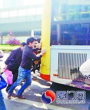 厦门一公交车半路熄火 乘客下车合力推车高清图片