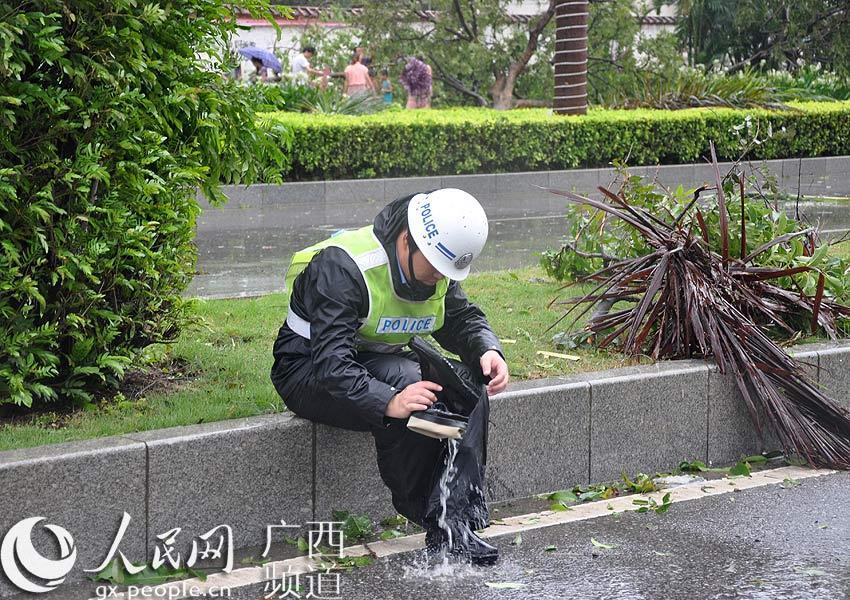 一位交警在路�休�B�r,�⑺�鞋中的水倒出