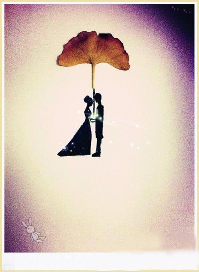 女孩捡鲜黄银杏叶做创意树叶画 温暖友情(图)图片