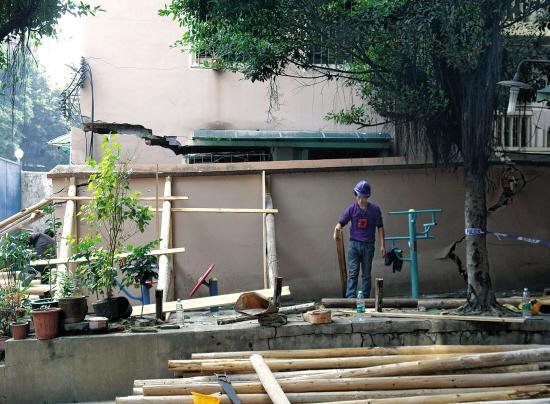 昨日,抢修工人用木头支撑开裂倾斜的墙体,以防止其继续下陷.